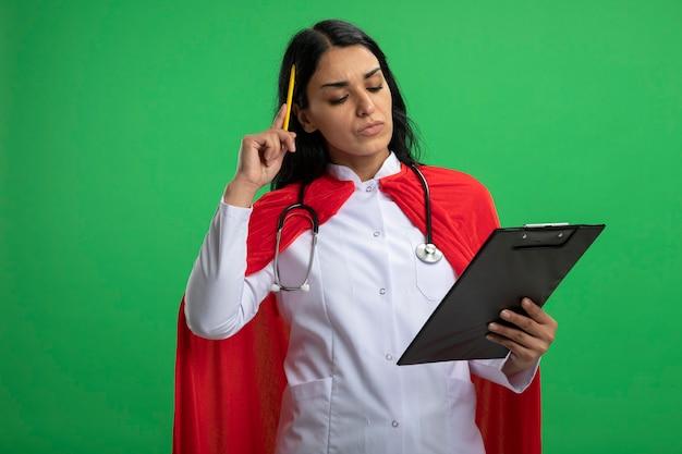 Задумчивая молодая девушка супергероя в медицинском халате со стетоскопом, держащая и смотрящая в буфер обмена, кладя ручку на голову, изолированную на зеленом