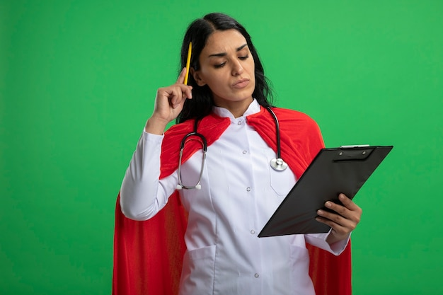 Pensieroso, giovane, supereroe, ragazza, il portare, medico, tunica, con, stetoscopio, presa a terra, e, guardando, appunti, mettere, penna, su, testa, isolato, su, verde