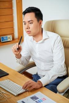 彼のオフィスの机でコンピューターに取り組んで、新しいデザインを作成している物思いにふける若いuxデザイナー