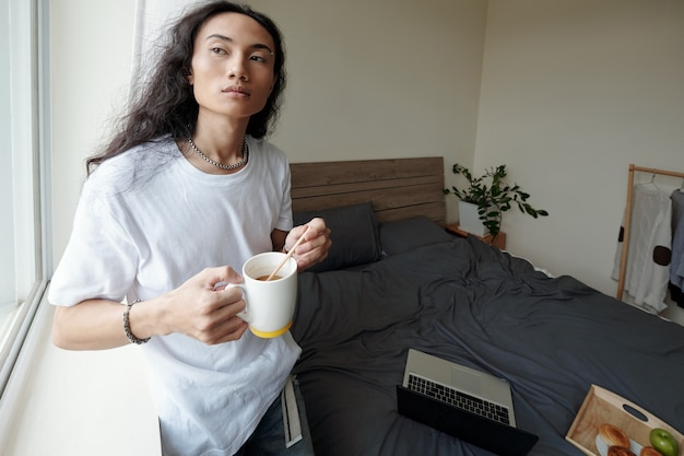 Pensive young vietnamese man in wavy hair standing at window and stirring sugar in coffee cup, he working remotely at home