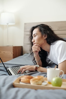 Pensive young vietnamese online manager with long hair lying on bed with breakfast on tray and using laptop while thinking of project