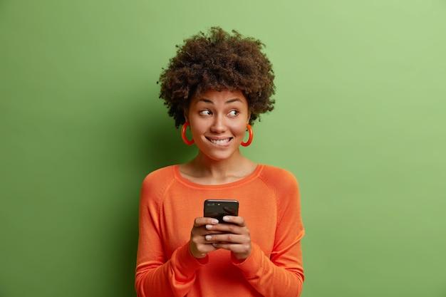 物思いにふける若い女性が唇を噛む現代の携帯電話の使用を保持モバイルフィーはテキストメッセージを送信しますオレンジ色のジャンパーと緑の壁に隔離されたイヤリングを着用します