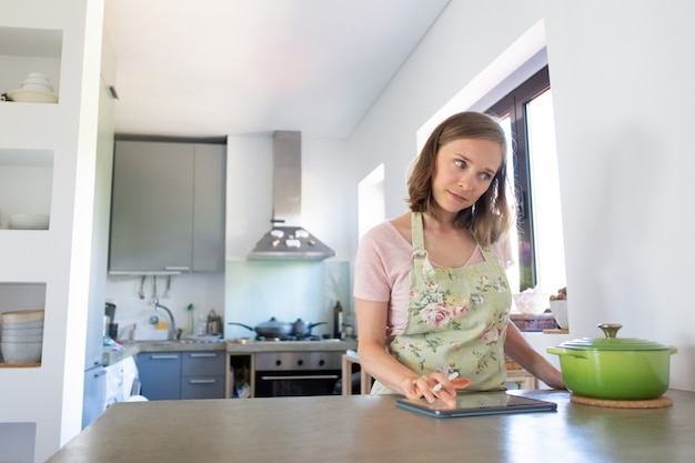 カウンターで大きな鍋の近くのタブレットを使用して彼女のキッチンで調理している間インターネットをコンサルティング物思いにふける若い女性。正面図。家庭料理とオンライン料理のコンセプト
