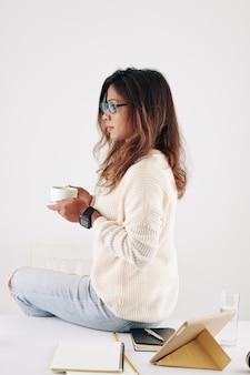 하루 종일 책상에서 일한 후 짧은 휴식을 즐길 때 커피 한 잔을 마시는 생각에 잠긴 젊은 여성