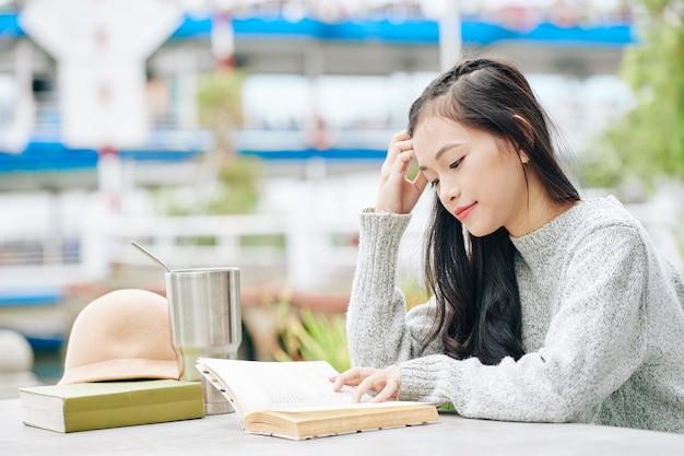 再利用可能なカップから飲んで、屋外で面白い本を読んで物思いにふける若い女性