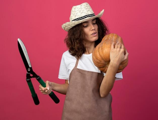 Pensieroso giovane donna giardiniere in uniforme che indossa il cappello da giardinaggio tenendo i clippers e mettendo la zucca sulla spalla isolato sul rosa