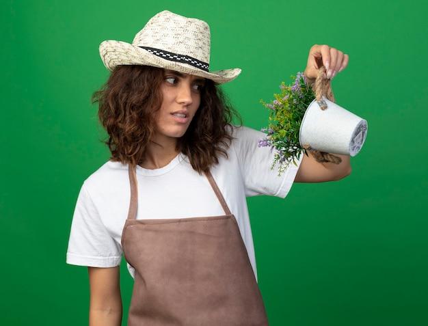 Giardiniere pensieroso della giovane donna in uniforme che porta il cappello di giardinaggio che tiene e che esamina il fiore in vaso di fiori isolato sul verde