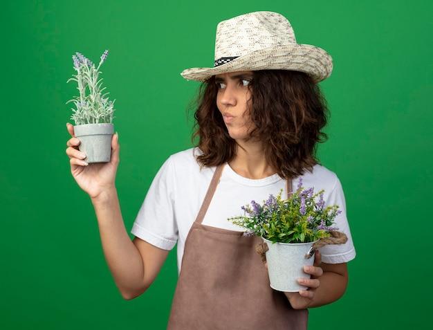 Pensieroso giovane donna giardiniere in uniforme che indossa cappello da giardinaggio tenendo e guardando i fiori in vasi da fiori isolati su verde