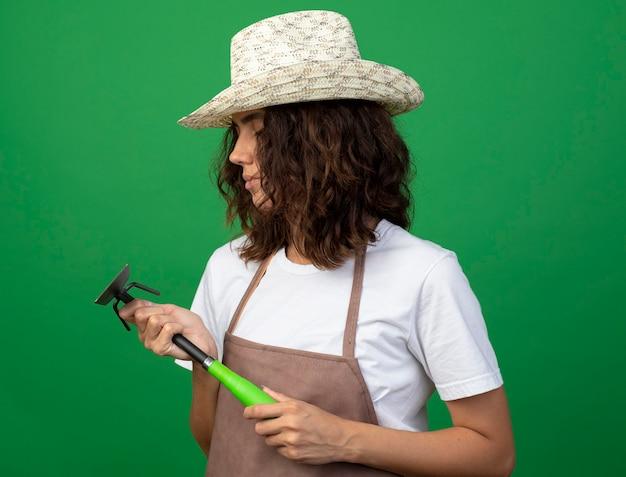Pensieroso giovane donna giardiniere in uniforme che indossa cappello da giardinaggio tenendo e guardando zappa rastrello isolato sul verde