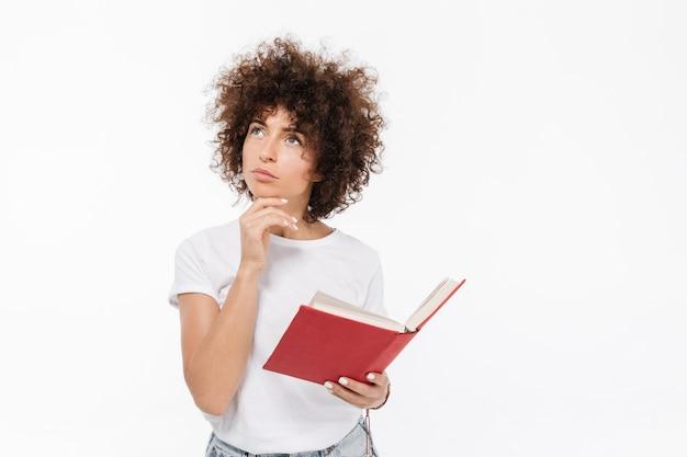 Задумчивая молодая женщина держа книгу и смотря прочь