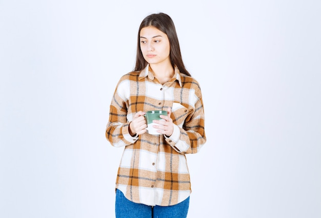 Pensive young woman holding cup of coffee on white wall.