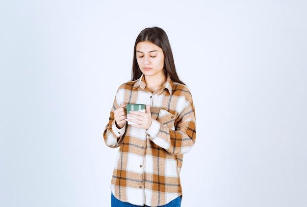 白い壁にコーヒーのカップを保持している物思いにふける若い女性。