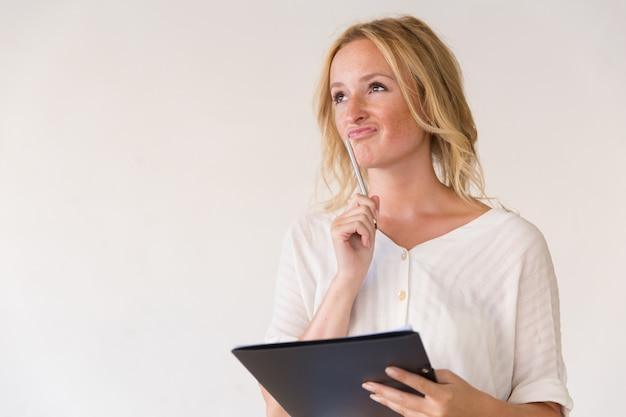 Задумчивая молодая женщина держа ручку и папку