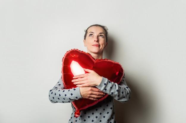 明るい背景にセーターとハートの気球で物思いにふける若い女性。バレンタインデーのコンセプト。バナー。