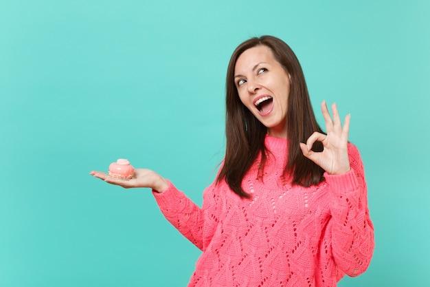 Задумчивая молодая женщина в вязаном розовом свитере, глядя вверх, показывая жест ок, держит в руке торт, изолированный на синем бирюзовом стенном фоне студийный портрет. концепция образа жизни людей. копируйте пространство для копирования.