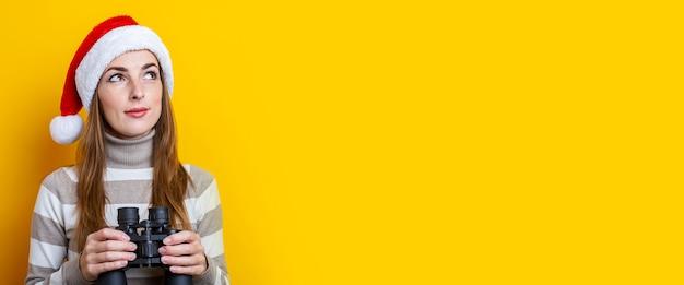 노란색 배경에 쌍안경으로 산타 클로스 모자에 잠겨있는 젊은 여자. 배너.