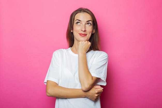 Задумчивая молодая женщина в белой футболке держит руку под подбородком