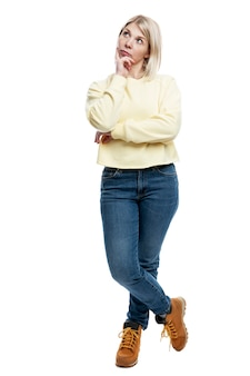 Pensive young woman in jeans and a yellow sweater. full height. isolated on white background. vertical.