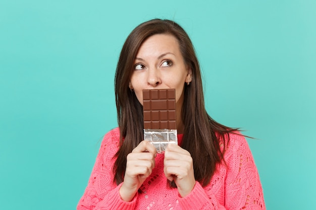 Pensive young woman in knitted pink sweater looking up, hold in hand, covering mouth with chocolate bar isolated on blue wall background, studio portrait. people lifestyle concept. mock up copy space.
