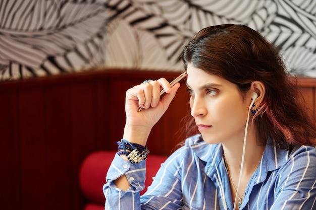 イヤフォンで音楽を聴き、カフェのテーブルに座って新しいプロジェクトのアイデアを熟考する物思いにふける若い女性