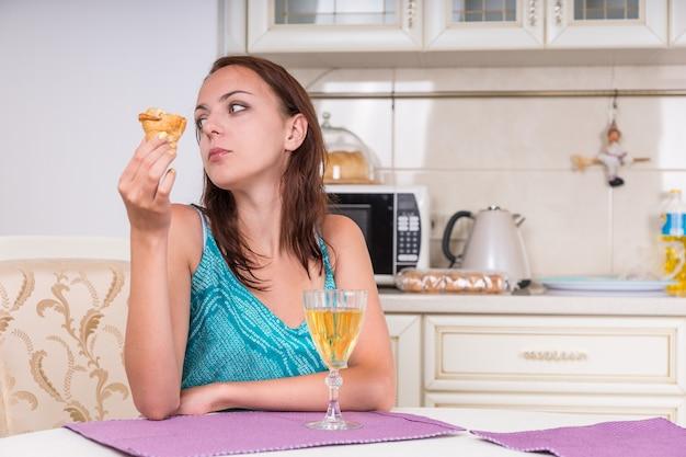 クッキーとワインと一緒に台所のテーブルに座って遠くを見ている物思いにふける若い女性