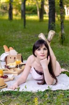 緑の芝生で横になっている物思いにふける若い女性。夏の晴れた日を楽しんでいます。健康食品、リラックスしたコンセプト