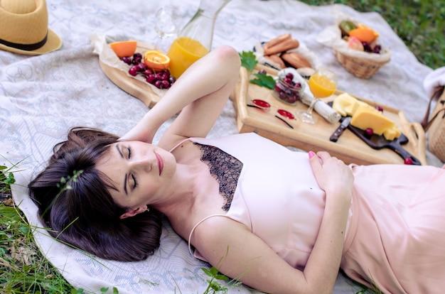 緑の芝生で横になっている物思いにふける若い女性。夏を楽しみ、夢を見る