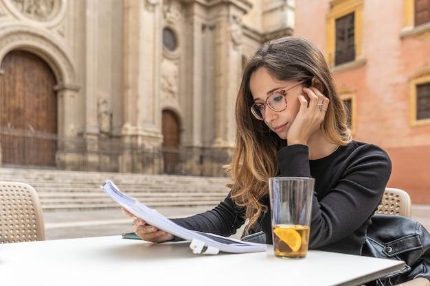 바 테이블에서 메모를 검토하는 잠겨있는 젊은 여성. 가로 사진