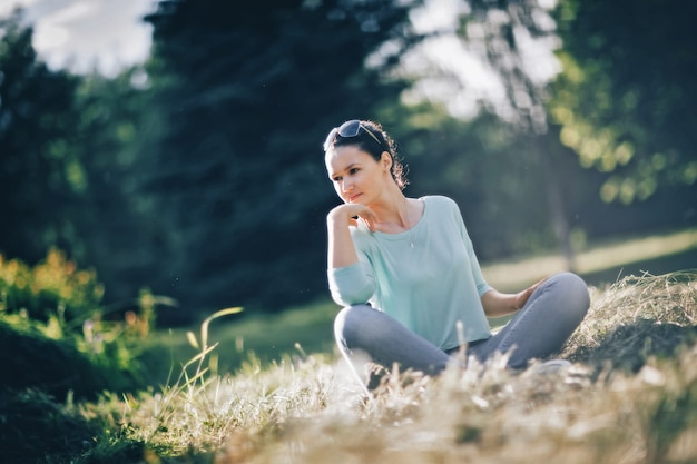 Pensive young woman sitting in lotus position in city park. photo with copy space