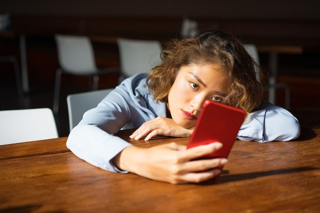 Pensive young woman surfing internet on phone