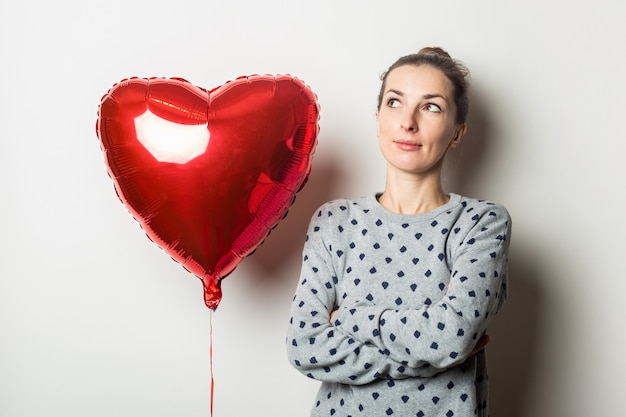 Pensive young woman in a sweater and a heart air balloon on a light background. valentine's day concept. banner.