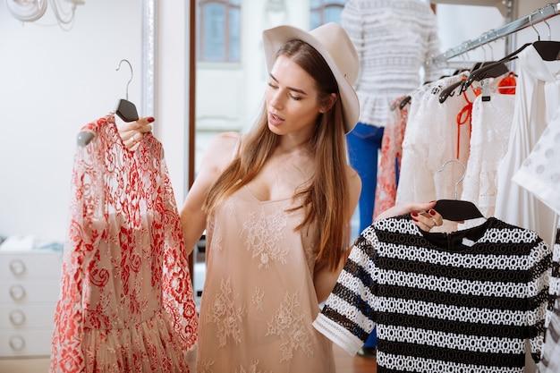 物思いにふける若い女性が店で服を考えて選ぶ