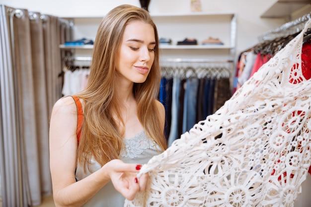 Задумчивая молодая женщина думает и выбирает платье в магазине