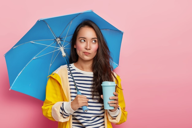 Pensive young woman with asian appearance, walks during rainy cloudy day under umbrella, drinks takeout coffee