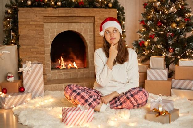 크리스마스 선물을 가진 잠겨있는 젊은 여성이 다리를 건너고 멀리보고 바닥에 앉아 사려 깊은 표정을 짓고 캐주얼하게 입고 턱 아래에 손가락을 유지하고 축제 거실에서 포즈를 취합니다.