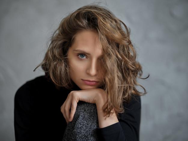 Задумчивая молодая женщина с вьющимися волосами подпирает руку подбородком