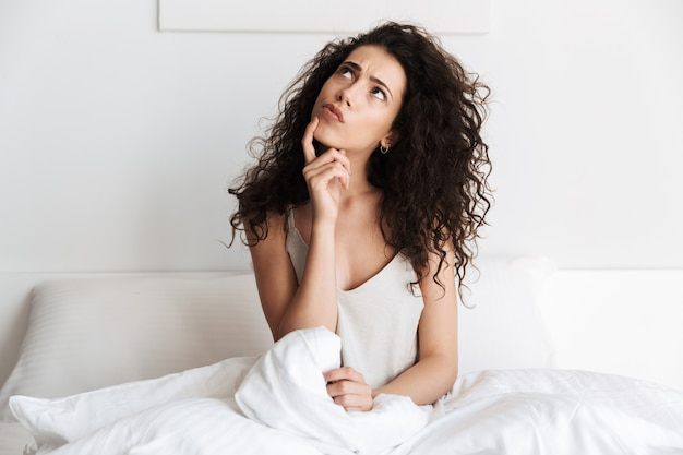 Pensive young woman with dark curly hair sitting