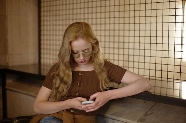 待合室に座っている携帯スマートフォンを持つ物思いにふける若い女性。