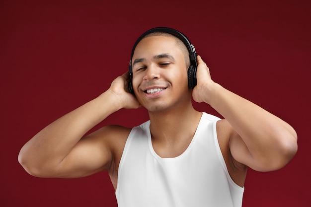 Peolple, 기쁨, 휴식, 엔터테인먼트 및 현대 기술 개념. 흰색 탱크 탑을 입고 새로운 무선 헤드폰으로 좋은 음악을 즐기는 쾌활한 긍정적 인 아프리카 남자의 격리 된 스튜디오 이미지