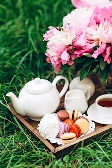Пионы, чайник и чашка чая на деревянном подносе