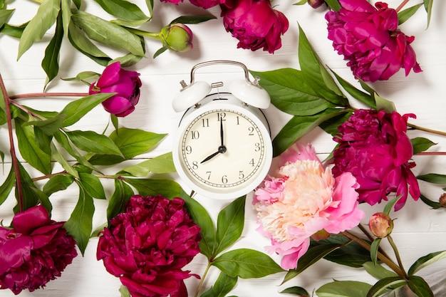 牡丹と木製の背景の目覚まし時計。