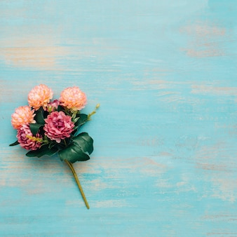 Peonies bouquet on blue wooden background.