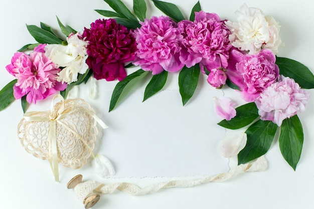 Peonies buds, a sheet of paper, a heart of lace and lace ribbon