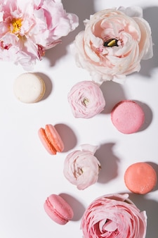 Peonies flowers with macaroons on white background top view