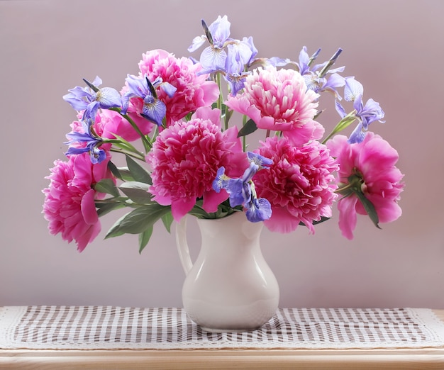 Peonies and irises in a jug on the table