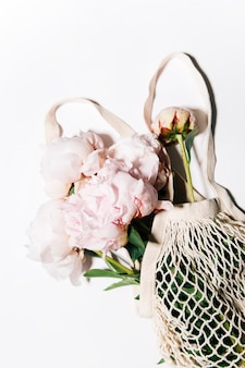 Peonies in a string bag on a white background