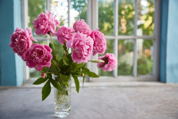 Peonies in a vase on the table against the background