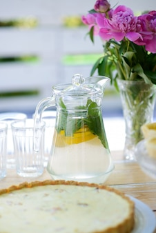 Ваза цветка пиона и стеклянный кувшин с лимонадом на деревянном столе для пикника в лете. семейный отдых.
