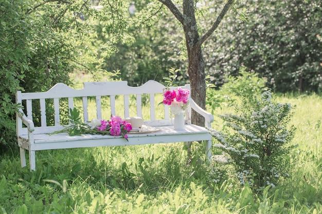 夏の庭の白い木製のベンチに水差しの牡丹