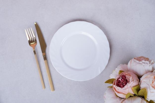Пионовидные розы, столовые приборы и тарелка на белой поверхности.